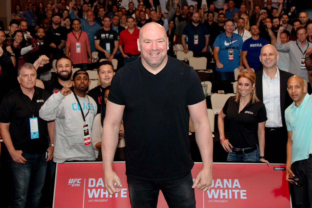 Dana White standing in front for a photo with people in the background