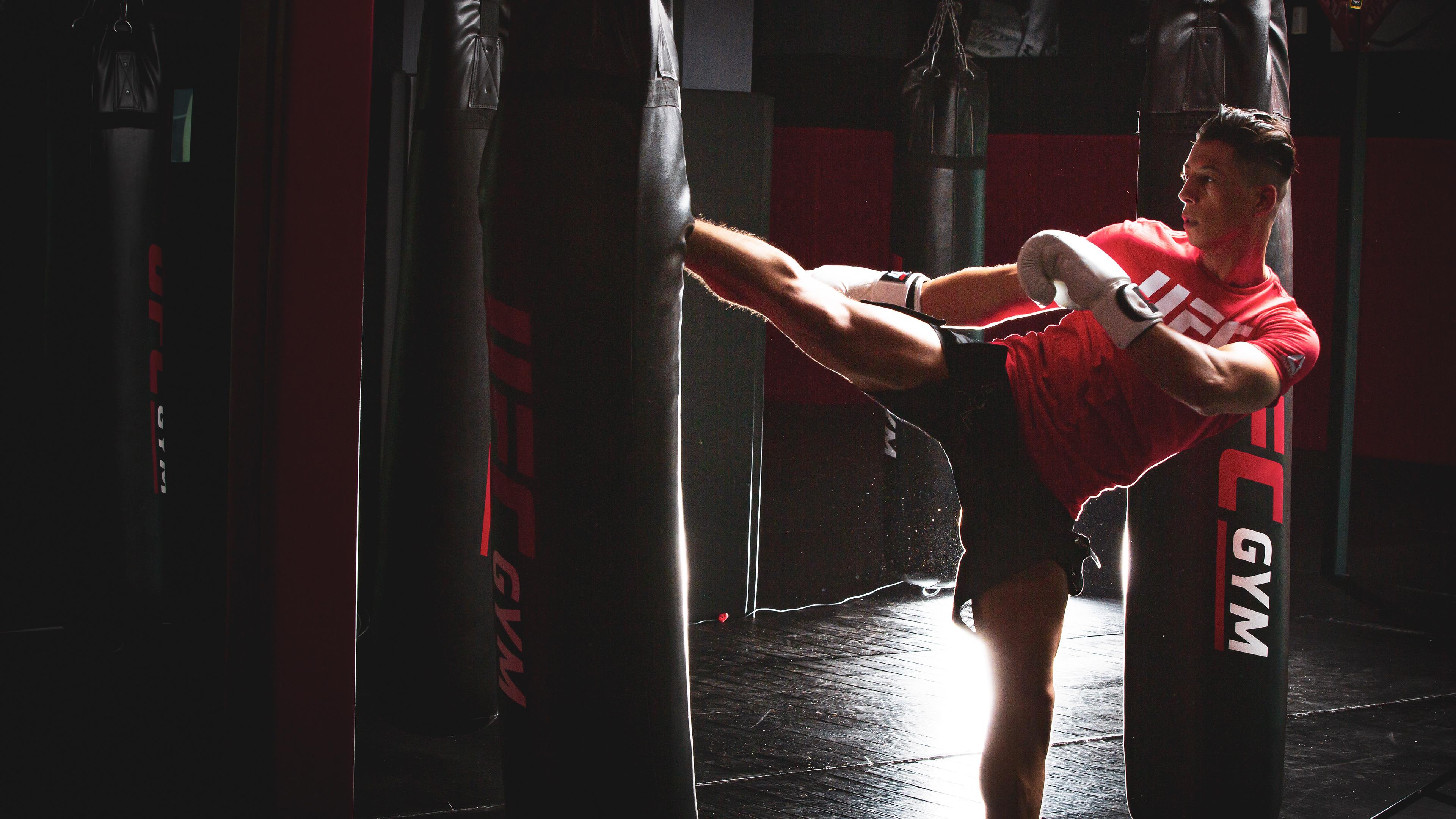 Amin kicking sandbag in kickboxing class